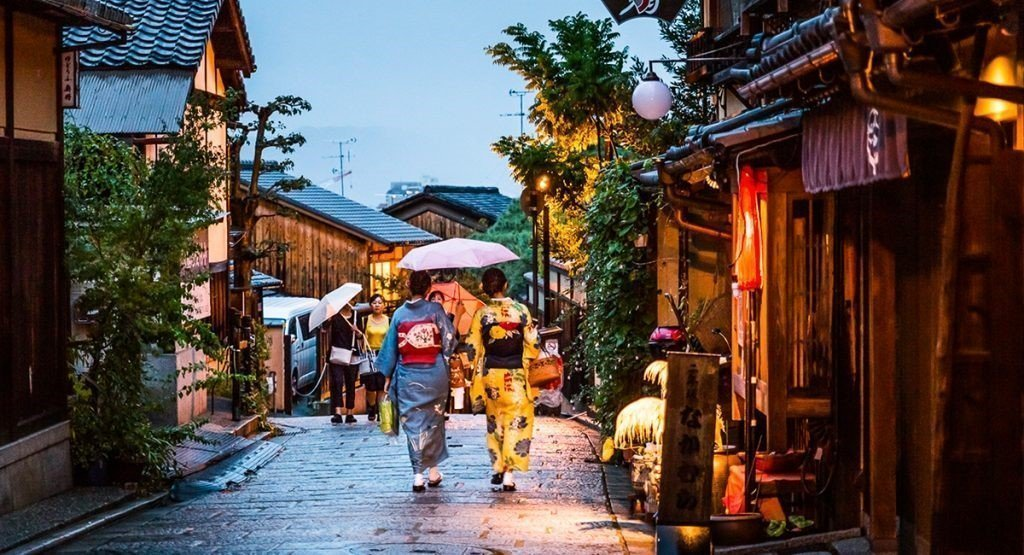 2 ladies dressed in traditional yukata robes stroll down a street in Higashiyama, Kyoto